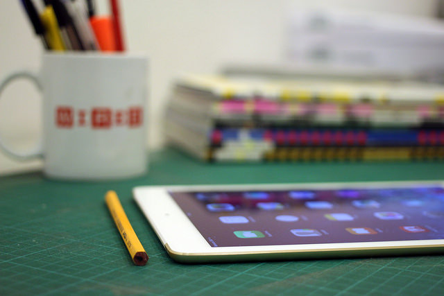 Photo of tablet on a desk with a cup of pens in the background